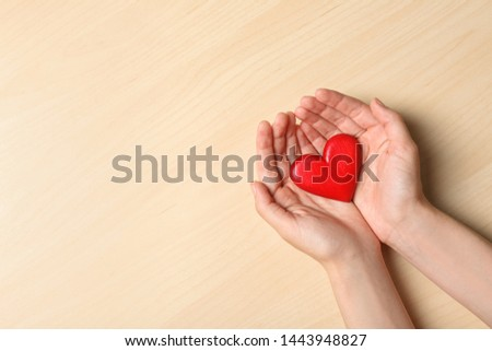 Woman holding heart on wooden background, top view with space for text. Donation concept #1443948827
