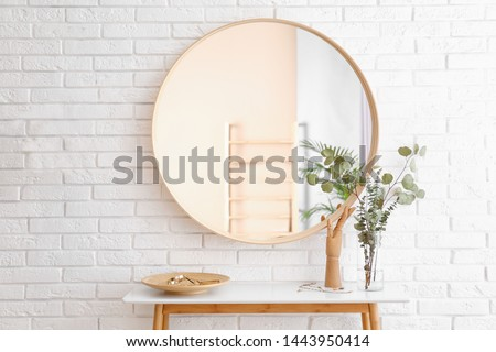 Big round mirror, table with jewelry and decor near brick wall in hallway interior Royalty-Free Stock Photo #1443950414