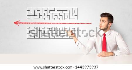 Businessman presenting a maze on a wall #1443973937