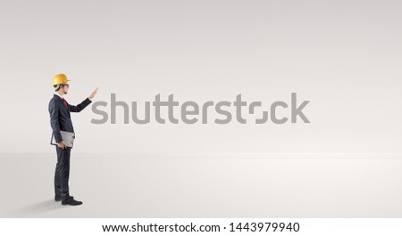 Young architect with construction helmet standing in an empty space and holding a plan #1443979940