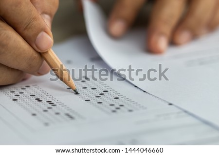 Education school test concept : Hands student holding pencil for testing exams writing answer sheet or exercise for taking fill in admission exam multiple carbon paper computer at university classroom #1444046660