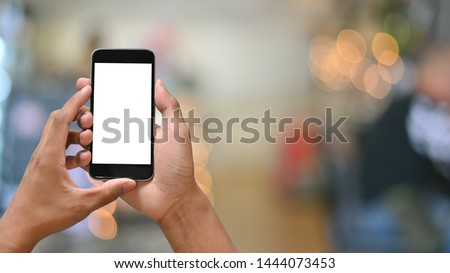 Smartphone on hands with empty screen and bokeh on blur background. #1444073453