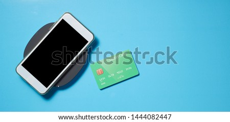 Smartphone mockup with credit card on blue backgroundม Business concept