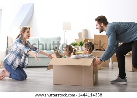 Young couple playing with children indoors. Happy family on moving day #1444114358