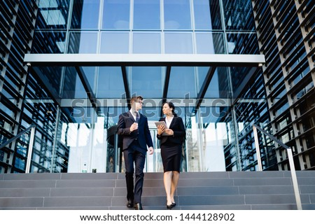 From below of multiethnic woman and man in suits holding coffee cup and tablet walking down steps of office building and talking #1444128902