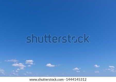 clear blue sky with tiny white clouds above the horizon. Natural background, sky over the boundless sea, wide angle. Sunny cloudscape #1444145312