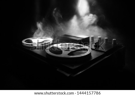 Old vintage reel to reel player and recorder on dark toned foggy background. Analog Stereo Open Reel Tape Deck Recorder Player with Reels. Selective focus #1444157786