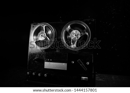 Old vintage reel to reel player and recorder on dark toned foggy background. Analog Stereo Open Reel Tape Deck Recorder Player with Reels. Selective focus #1444157801