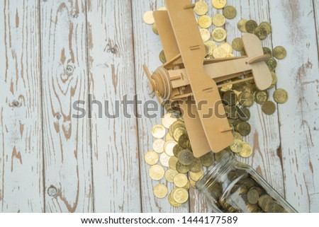 Wooden Airplane toy and jar of coins on vintage wooden table with copy space.Travel concept. #1444177589