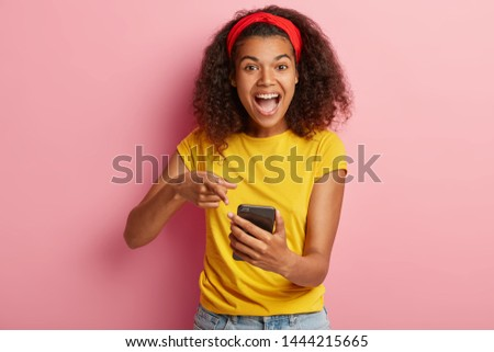 Joyful beautiful curly woman points at smartphone device with fast internet connection, views photos in social networks, wears yellow clothes, stands against rosy background. Selective focus. #1444215665