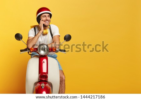 Happy man courier poses on fast motorbike, talks via cell phone during rest, carries rucksack, wears helmet, looks aside with pleased expression, isolated on yellow wall. People, technology, transport #1444217186