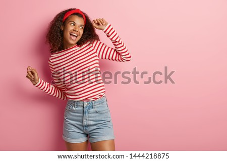Active energized Afro woman dances and has fun, feels amused and upbeat, looks happily aside, performs victory dance, likes music rhythm, wears fashionable apparel, isolated on rosy studio wall #1444218875