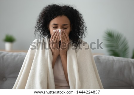 Ill african young woman covered with blanket blowing running nose got fever caught cold sneezing in tissue sit on sofa, sick allergic black girl having allergy symptoms coughing at home, flu concept #1444224857