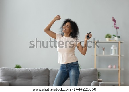 Happy funky carefree african american girl holding smartphone at home listening good music playing in mobile app, smiling active black young woman dancing alone having fun with phone in apartment #1444225868