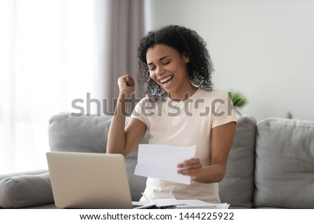 Excited overjoyed black girl student holding mail paper admission letter bank statement, happy euphoric african woman read good news get new job scholarship, celebrate loan approval great test result #1444225922