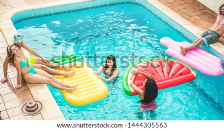 Young friends floating with air lilos inside swimming pool - Happy people having fun on summer holidays vacation - Travel, friendship, youth and tropical concept - Focus on asian girl face #1444305563