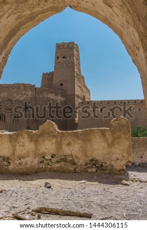 Historical clay Oman fort. View on a tower from arch. Blue sky.  #1444306115