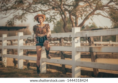 Asian girl in a cowgirl outfit standing at the farm fence.