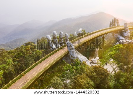 "Top aerial view of the famous Golden Bridge is lifted by two giant hands in the tourist resort on Ba Na Hill in Da Nang, Vietnam. "" Cau Vang"" is a favorite destination for tourists #1444320302"