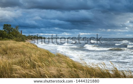 Thunderstorm over Baltic sea in a windy summer evening. Impressive waves hitting breakwater. Lighthouse covered in dark storm clouds above. Sandy seashore covered in tall grass. #1444321880