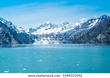 A distant view of Margerie Glacier, Alaska.  Icebergs from the glacier are floating on the water surface in the foreground and snow capped mountains in the background.   #1444331042