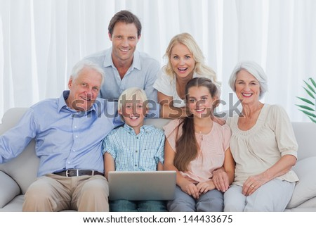 Extended family sitting on couch and using a laptop #144433675