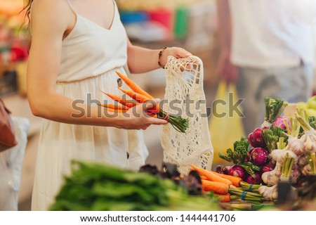 Female hands puts fruits and vegetables in cotton produce bag at food market. Reusable eco bag for shopping. Zero waste concept. #1444441706