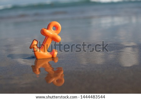 Close up picture of a small orange anchor beach toy placed in the shallow water at the Batu Bolong beach in Canggu, Bali
