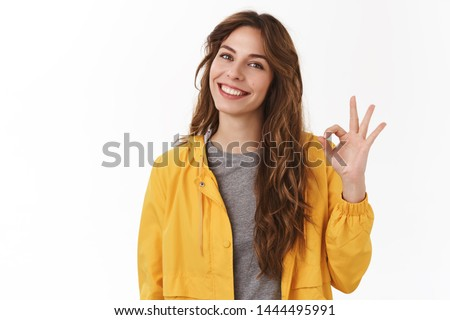 Good job. Pretty carefree modern stylish caucasian girl long chestnut hair show okay ok approval sign smiling toothy tilting head pleased give positive reply like excellent service, white background #1444495991