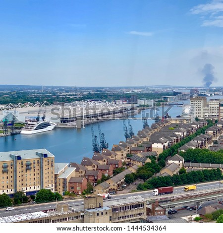 Greenwich, UK - 5 July 2019: View of the Excel centre from the Emirates Air Line cable car. The smoke in the distance is from a fire in Rainham, Essex, 12 miles away. #1444534364