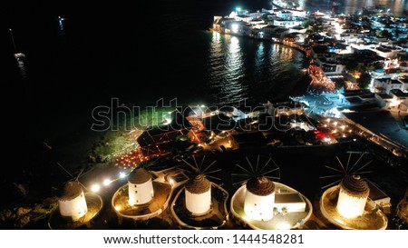 Aerial drone night shot of iconic and picturesque illuminated windmills in main town of Mykonos island, Cyclades, Greece #1444548281