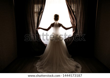 the bride in a wedding dress with a train opens the curtains of the window, stands back, you can see her silhouette, against the light, space for text