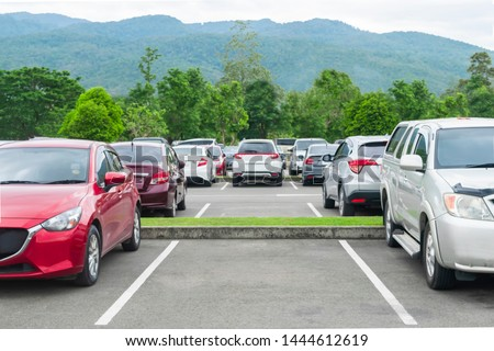 Car parked in asphalt parking lot and empty space parking  in nature with trees and mountain background .Outdoor parking lot with fresh ozone and eco friendly green environment concept #1444612619