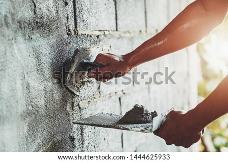 closeup hand of worker plastering cement at wall for building house                                 #1444625933