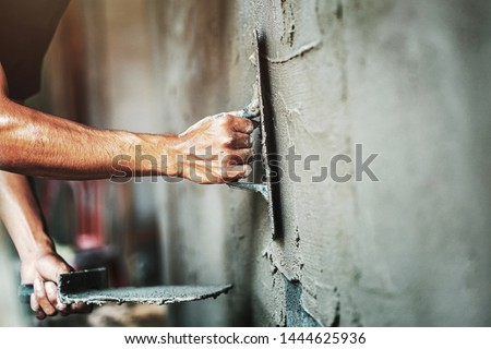 closeup hand of worker plastering cement at wall for building house                                 #1444625936