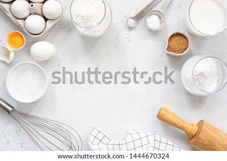 Frame of baking and cooking bread pastry or cake ingredients, flour sugar milk eggs and coconut butter on bright grey background with copy space for text, flat lay Royalty-Free Stock Photo #1444670324