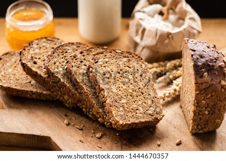Sliced rye bread with sunflower seeds on rustic wooden background. Healthy food still life #1444670357