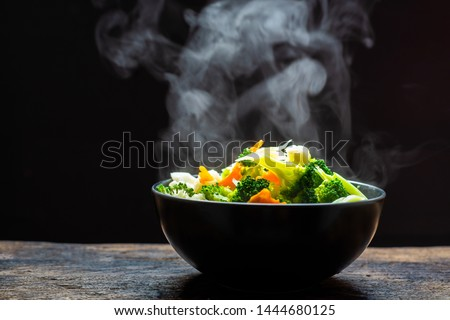 The steam from the vegetables carrot broccoli cauliflower on black bowl , a steaming. Boiled hot Healthy food on table on black background,hot food and healthy meal concept #1444680125
