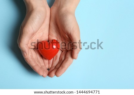 Woman holding heart on blue background, top view with space for text. Donation concept #1444694771