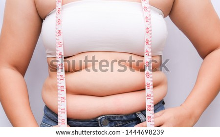 Beautiful fat woman with tape measure She uses her hand to squeeze the excess fat that is isolated on a white background. She wants to lose weight, the concept of surgery and break down fat under the  #1444698239