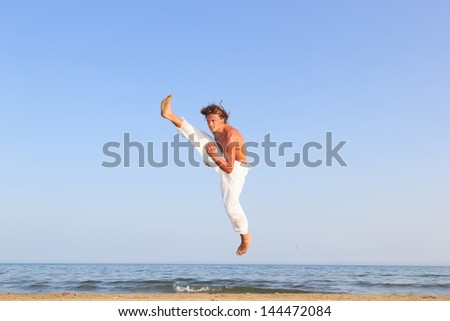 Young adult man  practicing a Kata on the beach on a sunny day #144472084