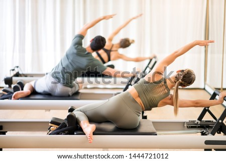 Group of people doing the mermaid pilates exercise or side stretch to tone the intercostal muscles viewed from the rear #1444721012