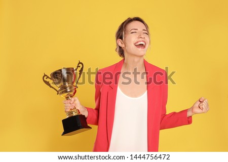 Portrait of happy young businesswoman with gold trophy cup on yellow background Royalty-Free Stock Photo #1444756472