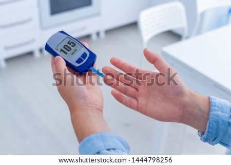 A diabetic patient measures blood glucose with a glucose meter at home. Woman having diabetes, control and analyze glucose blood level #1444798256