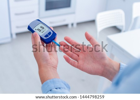 A diabetic patient measures blood glucose with a glucose meter at home. Having diabetes and control glucose blood level  #1444798259