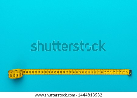 Top view of yellow soft measuring tape. Minimalist flat lay image of tape measure with metric scale over turquoise blue background with copy space. Photo of body measuring tape as diet concept. #1444813532