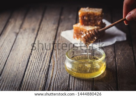 Honey dripping from honey dipper in glass jar with honeycomb over dark background. #1444880426