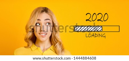 Waiting for new year. Blonde biting her lip and looking at 2020 loading process, yellow panorama background #1444884608