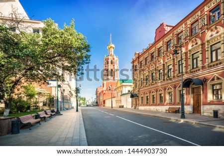 The bell tower of the Petrovsky Monastery in Moscow and benches under the trees on a sunny summer morning #1444903730