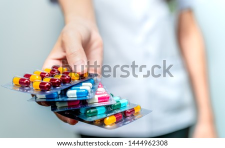 Pharmacist or doctor hand holding pack of antibiotic capsule pills and giving patient or people. Antibiotic drug overuse. Antimicrobial drug resistance. Community pharmacist. Drugstore background. #1444962308